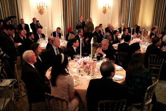Vice President Mike Pence, left, together with invited guests listen to President Donald Trump speak during a National Day of Prayer dinner gathering of faith leaders from the interfaith community in the State Dining Room of the White House in Washington, Wednesday, May 1, 2019.