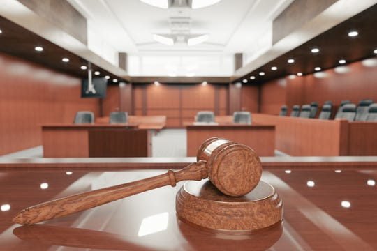 Interior of an empty courtroom with gavel and sounding block on the desk. [Via MerlinFTP Drop]
