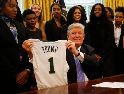 President Donald Trump holds a jersey at a ceremony honoring the 2019 women's NCAA basketball champion Baylor Lady Bears in the Oval Office at the White House, April 29, 2019.