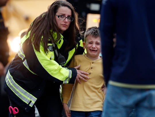 Officials guide students off a bus and into a recreation center where they are being reunited with their parents after a shooting at a suburban Denver middle school.