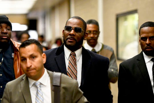 Musician R. Kelly, center, leaves the Daley Center after a hearing in his child support case Wednesday, May 8, 2019, in Chicago.