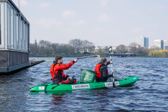 Volunteers collect trash in a GreenKayak.