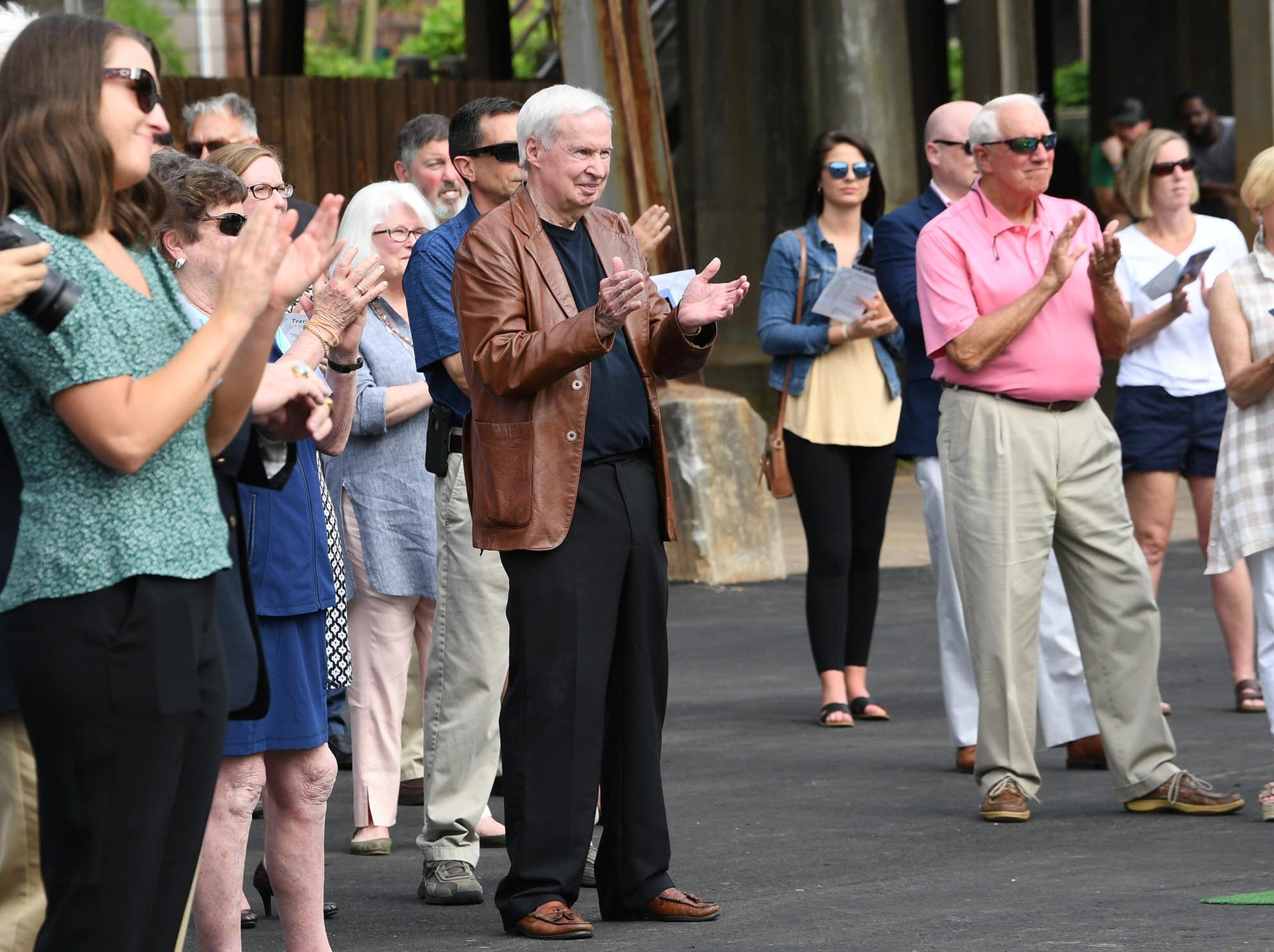 Andersonians applaud after officials unveil the Under the bridge project called Textile Point in downtown Anderson Thursday, May 9, 2019. Scott Foster of Anderson designed the monument honoring years of textile mills in Anderson, with support partners from To Benefit Anderson, South Carolina Heritage Corridor, the Rotary Club of Anderson, and the City of Anderson.