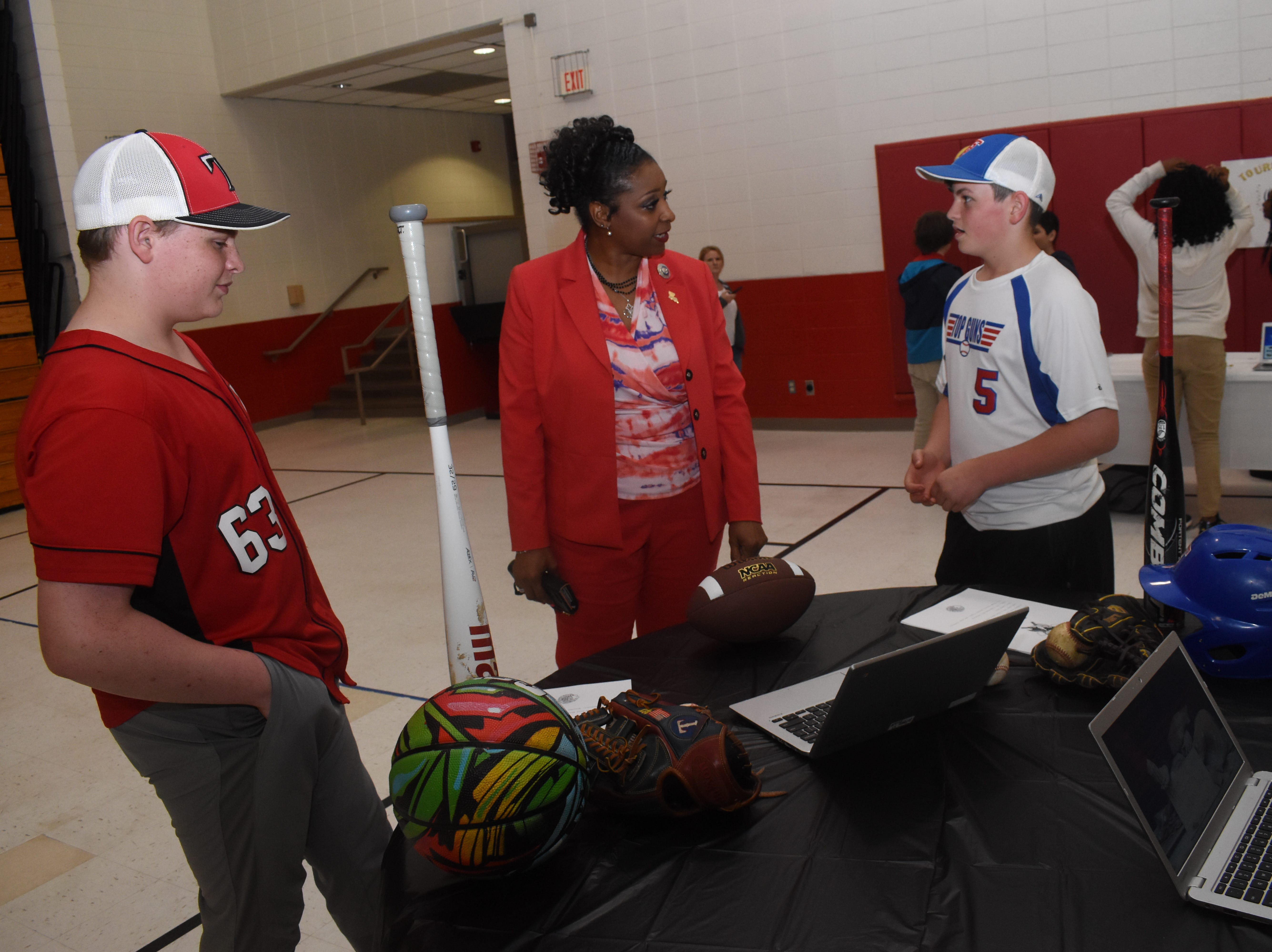 """Tioga Junior High School seventh-graders Brayden Timmer (left) and Blade Barrett (far right) talk with Vanessa Baptiste-McNeal, a legislative aide for La. State Sen. Jay Luneau, about their """"Genius Hour"""" project. The students told her that their project involved hosting a sports camp for people with special needs so they can participate in sports they otherwise would not be able to participate in. Brayden and Blade said they plan to host the camp in the summer of 2020 at the school. Tioga Junior High School seventh-graders presented projects to community members Thursday, May 9, 2019 in a class called Genius Hour. Students in the class were recommended by teachers. Janice Williams, a teacher at TJHS, said Genius Hour allows students to explore their own passions and encourages creativity in the classroom. The class allows students to choose what they would like to learn."""