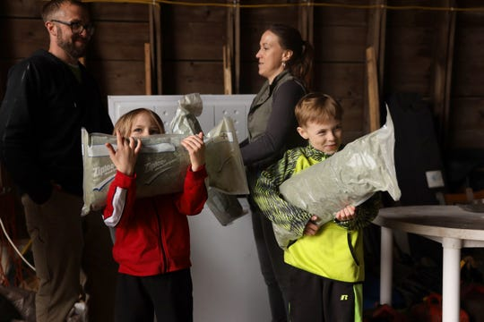 Ari Testaberg, 6, left, and Aki Testaberg, 8, show frozen hemp that was harvested last season and is now being stored in a freezer at their parents' hemp farm in River Falls on April 18. In the Testabergs' 1,000-square-foot processing facility, they can process 300 acres of hemp from their own land, as well as hemp grown by other farmers.