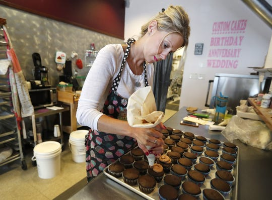 """Rebecca Henry, owner of Rebecca's Sweets Boutique, frosts cupcakes Thursday. The Appleton bakery will hand out free cupcakes Friday as part of a nationwide promotion from Facebook. The social media giant is debuting a new """"birthday stories"""" feature and teamed up with 50 bakeries across the country to help build some buzz."""