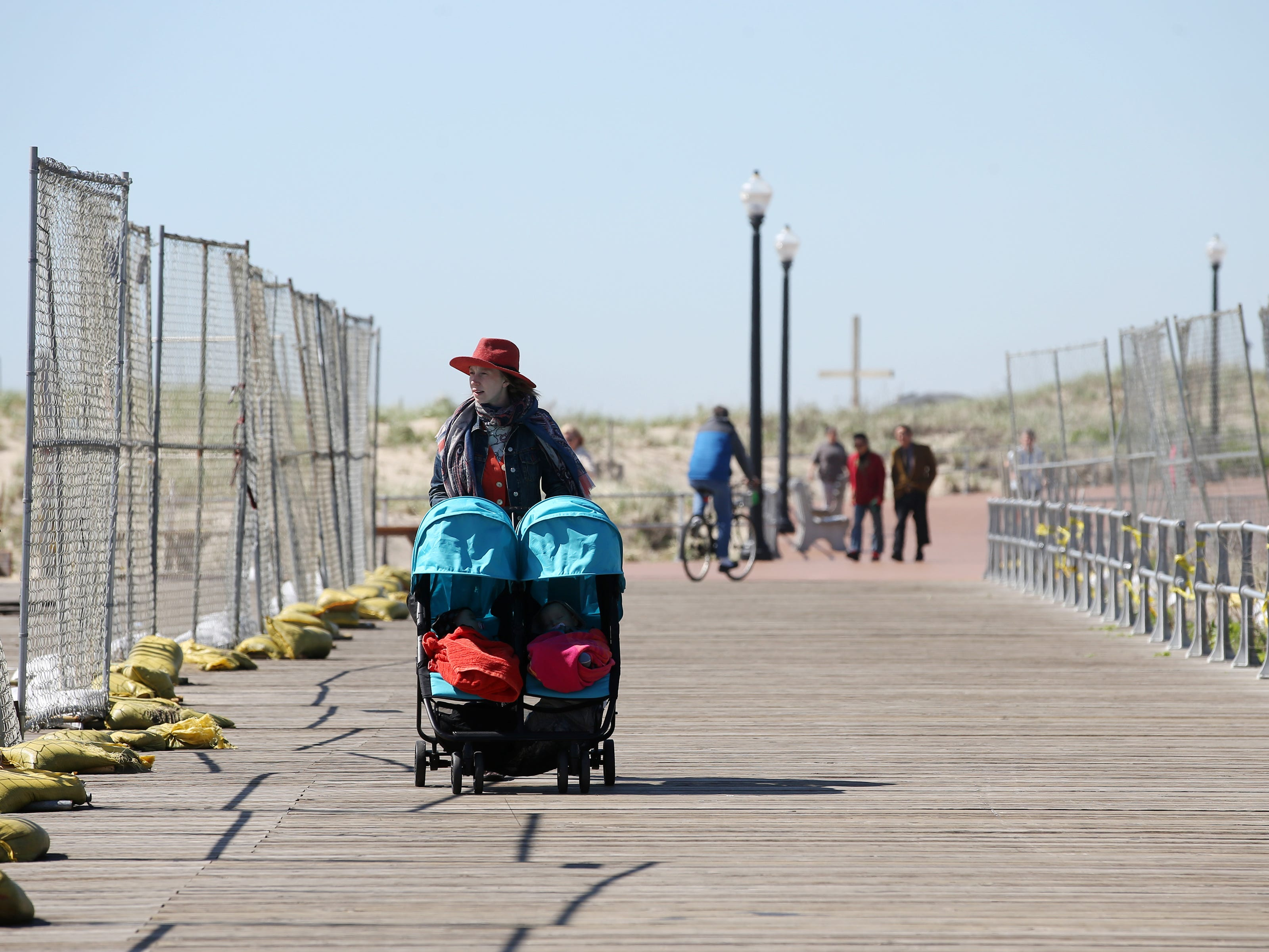 Megan Sipe of Brooklyn, New York walks along the boardwalk with her 8-month-old twins, Lola and Marlon Santiago, and looks at the remains of last month's beachfront pavilion fire during a sunny and mild morning in Ocean Grove, NJ Monday, May 6, 2019.