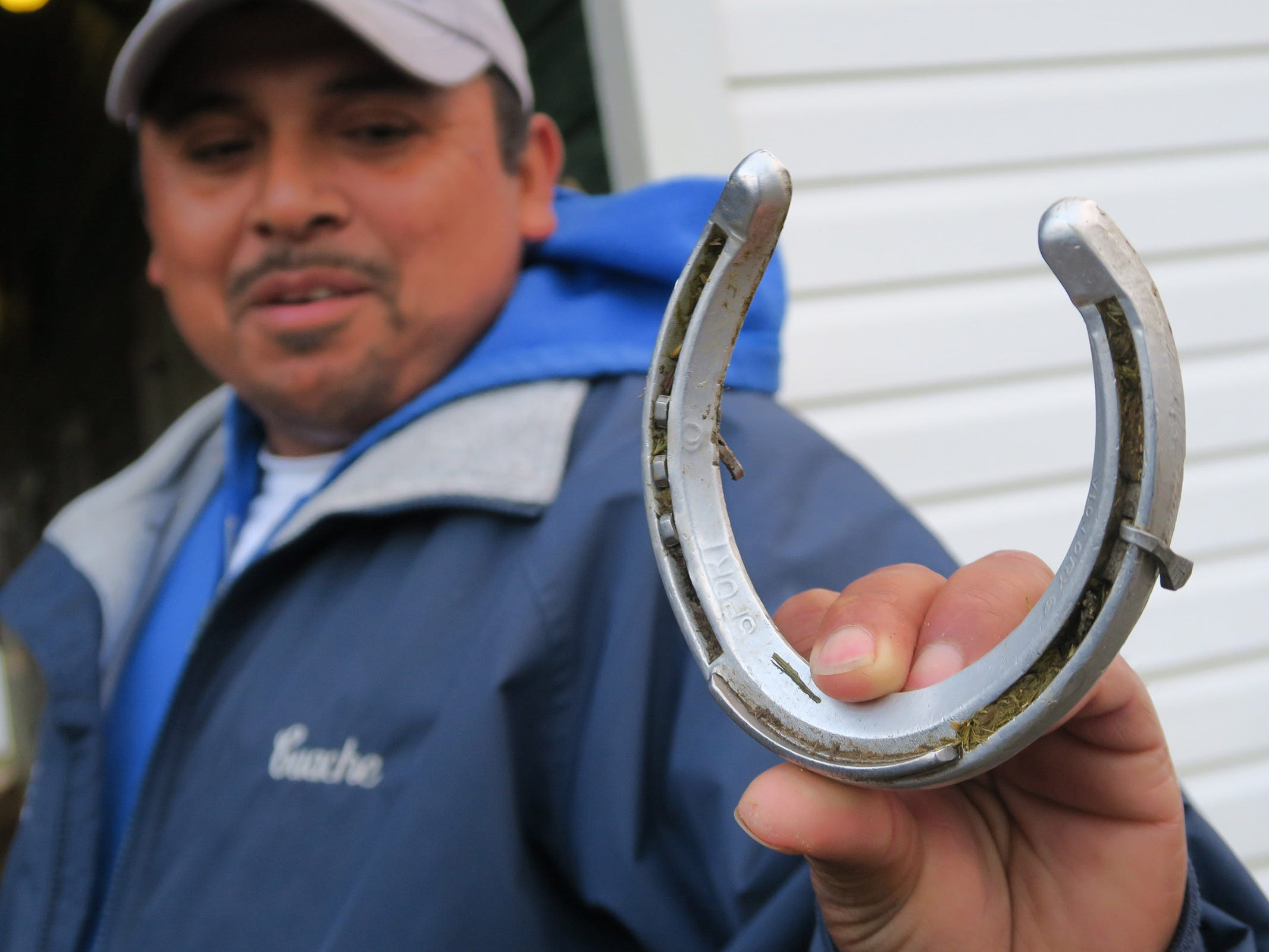 """Jose """"Guache"""" Hernandez holds a shoe from Maximum Security, disaqualified after winning the Kentucky Derby on Saturday, that came loose during his trip to Monmouth Park early Tuesday, May 7, 2019."""