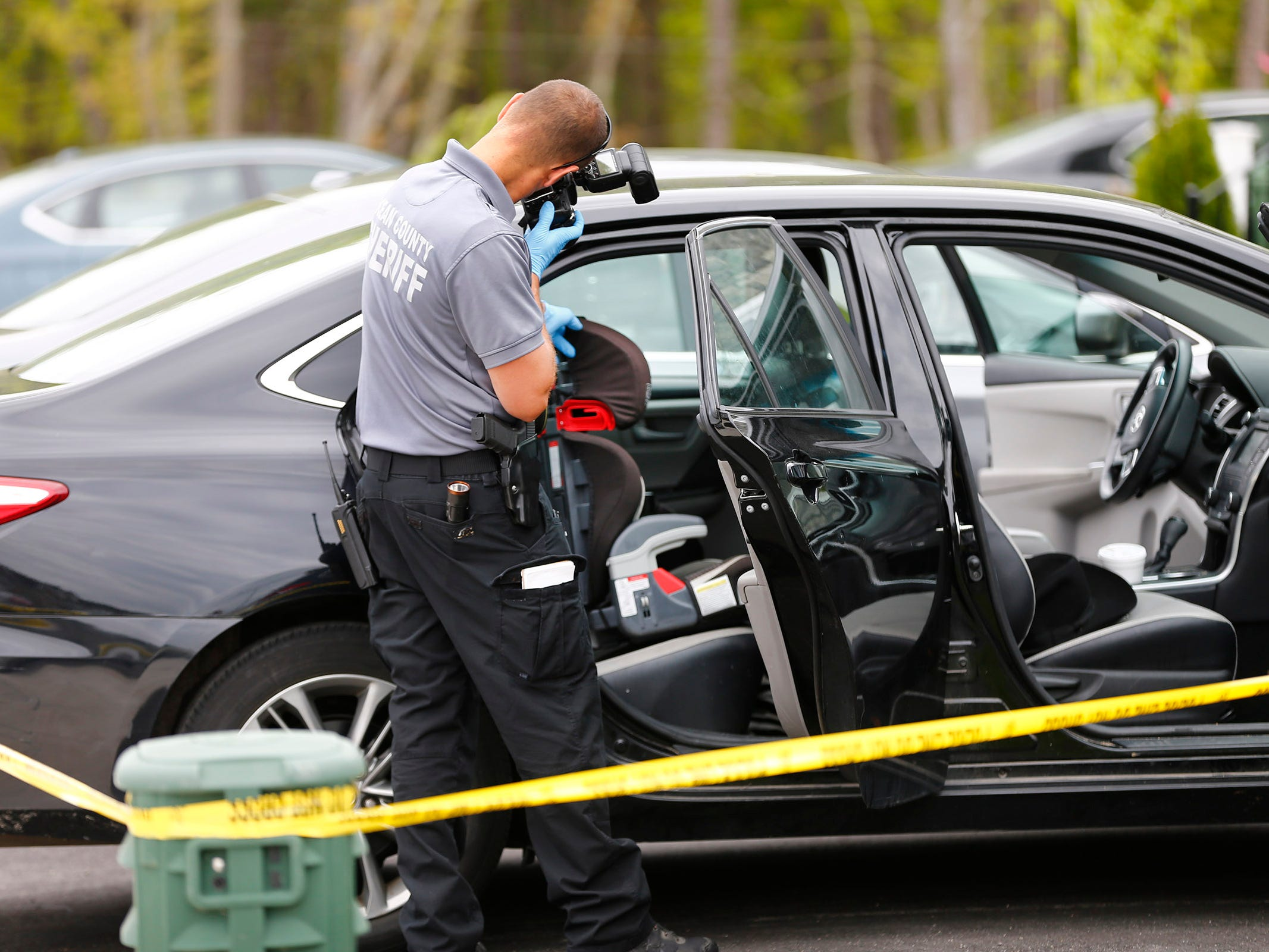 An Ocean County Sheriff's Department CSI officer photographs a car seat in the back seat of a car in the driveway at 18 Lewin Avenue in Lakewood Monday afternoon.  A baby was aledgedly found unresponsive in the car earlier and later died at the hospital.