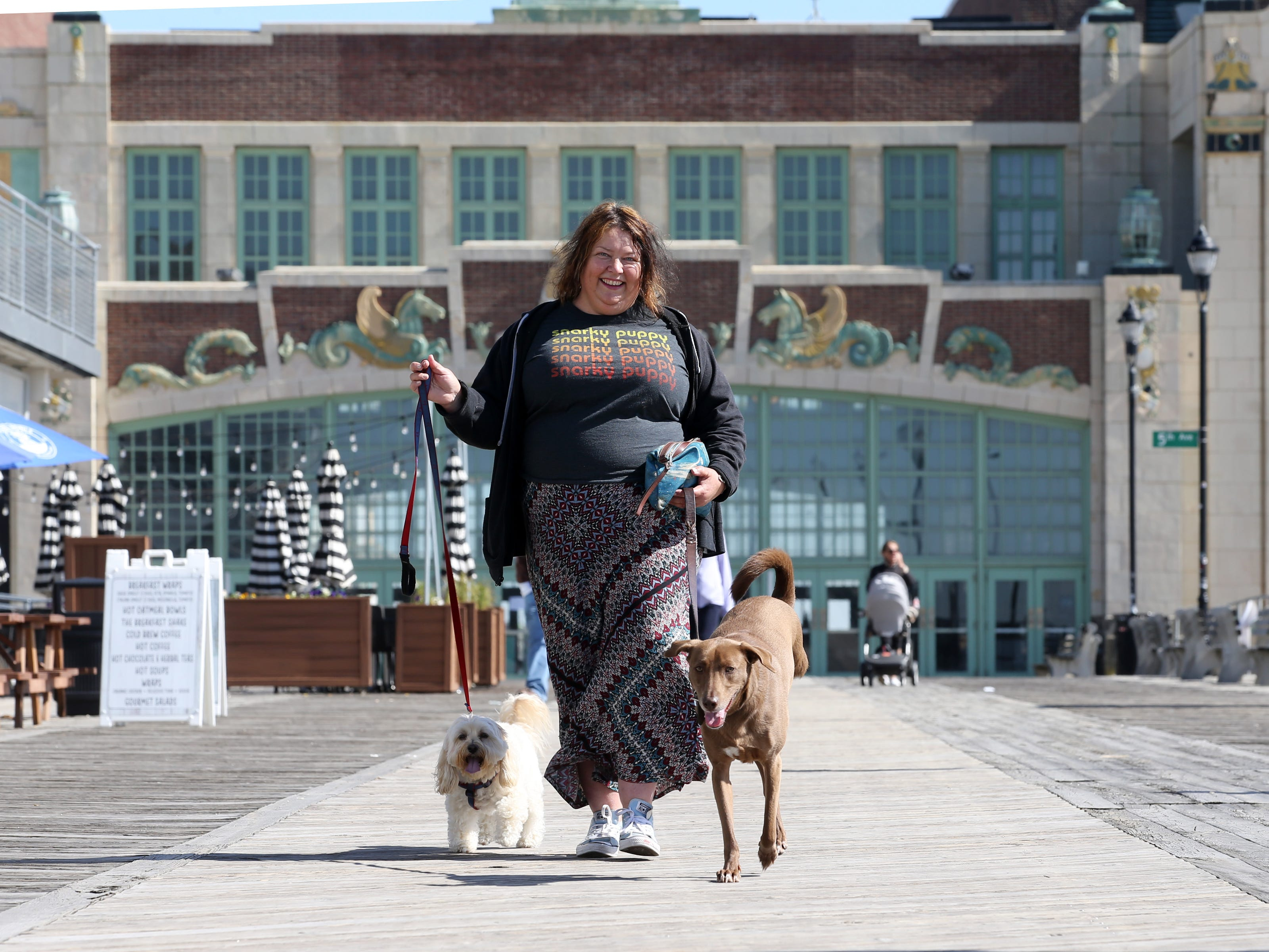 Kate Krisinski of Asbury Park, owner of Beach Baby Dog Care, walks Mango and Choco along the boardwalk during a sunny and mild morning in Asbury Park, NJ Monday, May 6, 2019.