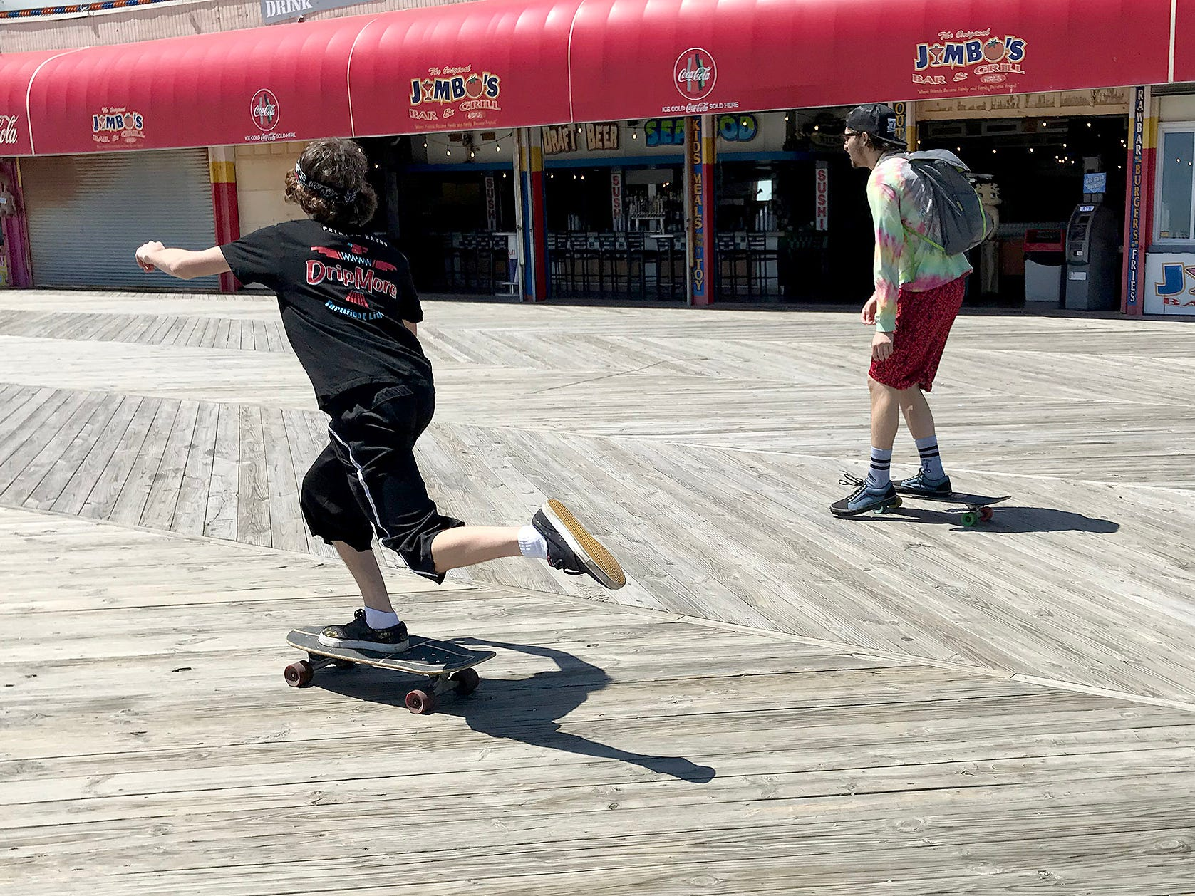 Two boys ride skateboards along the Seaside Heights boardwalk Monday, May 6, 2019.