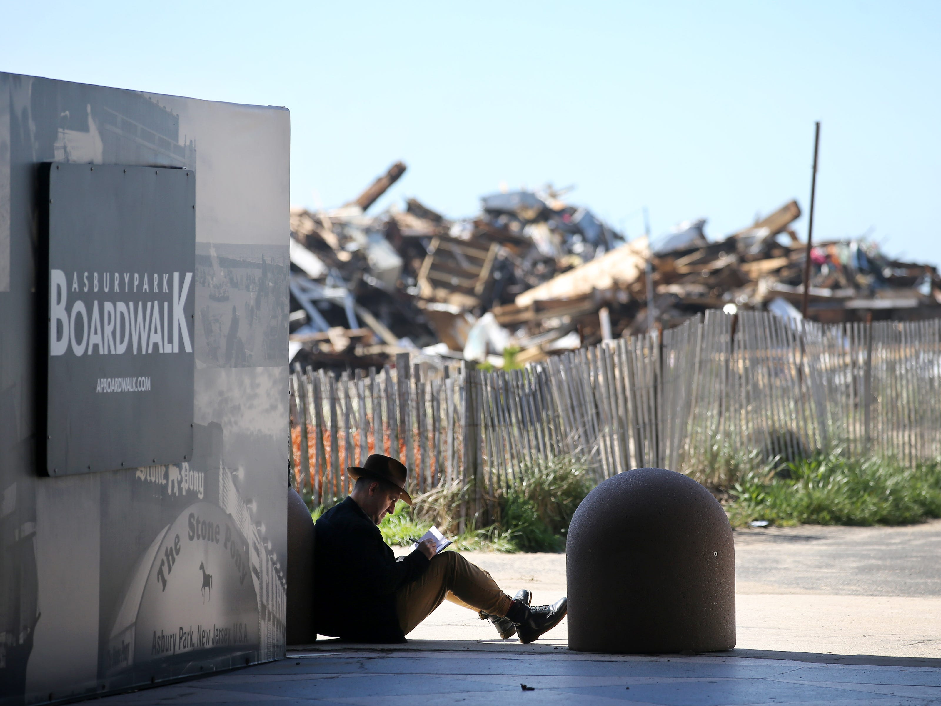 David Robert Donatucci of Los Angeles, California, who is visiting Asbury Park during a business trip, sits in the shade of the Casino building, with the remains of last month's beachfront pavilion fire in Ocean Grove behind him, as he sketches a picture of the steam plant during a sunny and mild morning in Asbury Park, NJ Monday, May 6, 2019.
