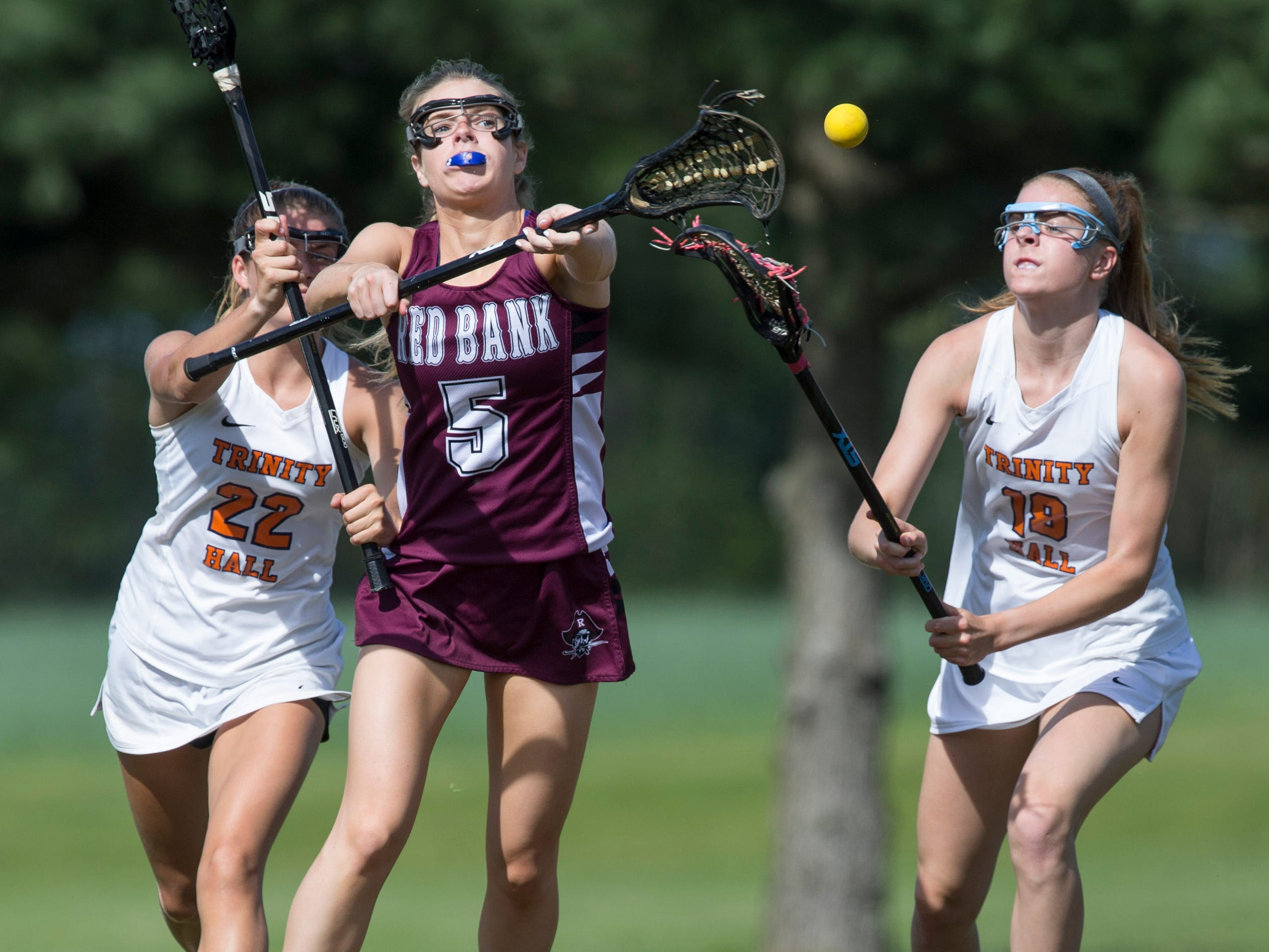 Red Bank Regional's B. Barnes passes the ball as Trinity Hall's Paige Nolan (22) and Caroline Gulka (18). Trinity Hall vs Red Bank Regional lacrosse. Colts Neck, NJTuesday, May 7, 2019