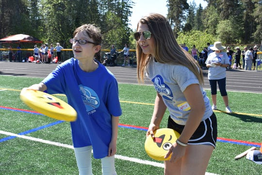 From left, Hannah Lockhart, 14, from Oakland Bay Junior High in Shelton starts to throw a Frisbee in a discus game with the help of North Mason High School senior volunteer Taylor Hendrickson. More than 70 North Mason High School students volunteered at the event and about 170 special needs students participated.
