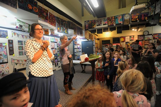 Director of Art In the Afternoon Stephanie Sulzman, right, and Amanda Riley welcome the attendees of the opening of the after-school program's art show in the Black Mountain-Tyson Library on May 6.