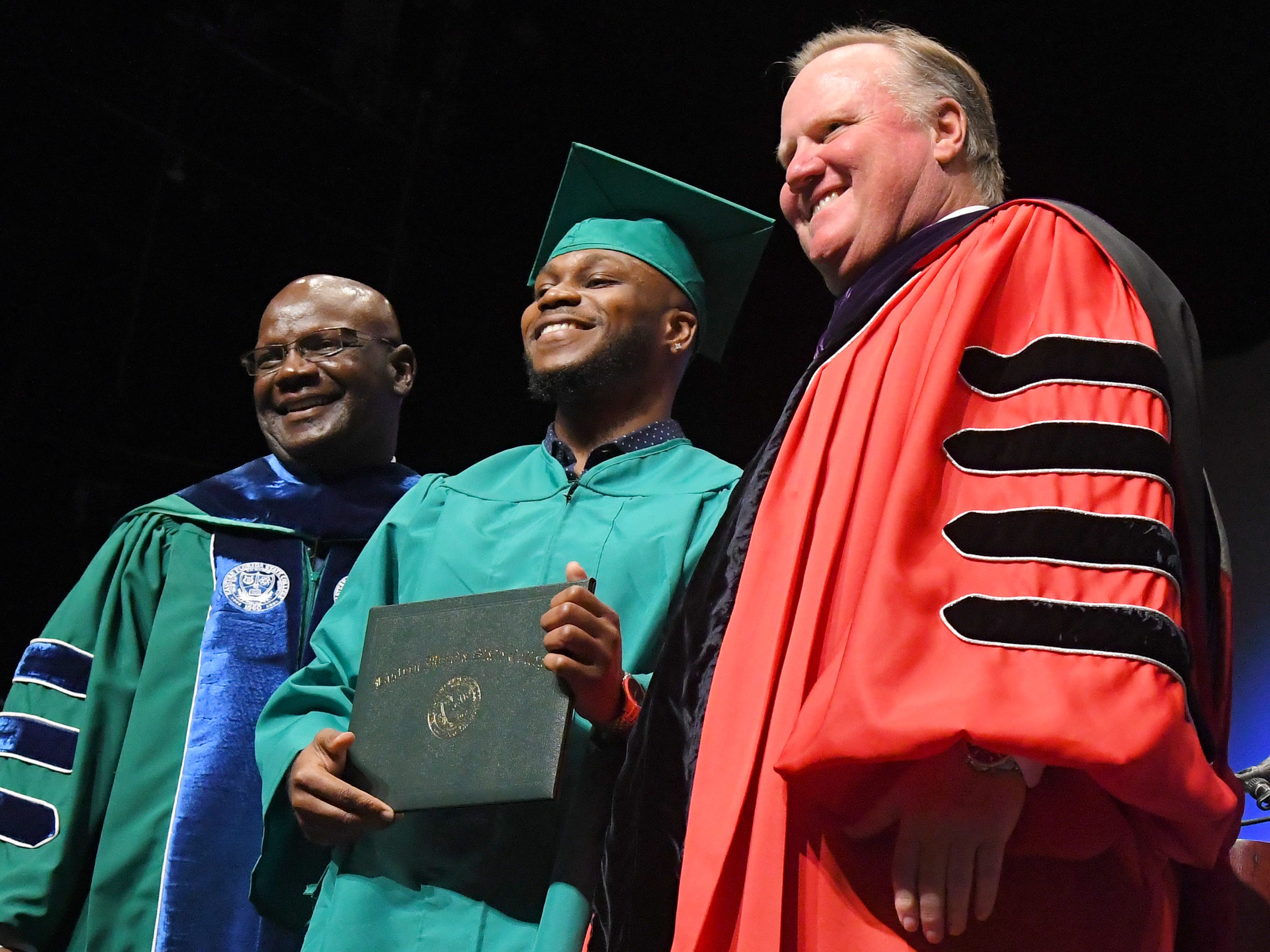 EFSC's 1,000th Bachelor's degree graduate is Derick Pierre, seen here flanked by Moses L. Harvin, Sr., of the Board of Trustees, and Jim Richey, president of EFSC. Graduates at the noon Eastern Florida State College 2019 Spring Commencement at the Melbourne campus. An additional commencement was held at 3:00 p.m.
