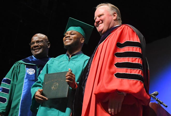 EFSC's 1,000 Bachelor's Degree graduate is Derick Pierre, seen here flanked by Moses L. Harvin, Sr., of the Board of Trustees, and Jim Richey, president of EFSC. Graduates at the noon Eastern Florida State College 2019 Spring Commencement at the Melbourne campus. An additional commencement was held at 3:00 p.m.