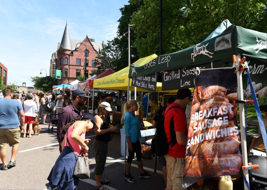 People line up for breakfast sandwiches at the Does' Leap stall set up on St. Paul Street at the Burlington Farmers Market at City Hall Park on Saturday, June 17, 2017.