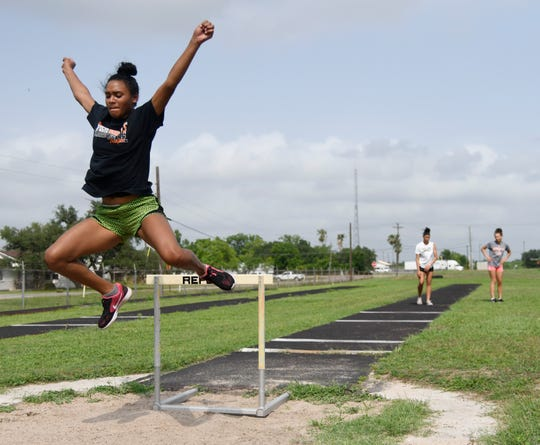 Alexa Valenzuela, left, practices her long jump while Tracelyn Ross and Jai'lin King wait, Wednesday, May 8, 2019, in Refugio.