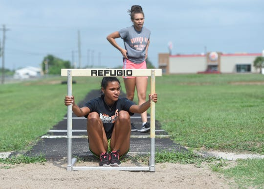 Alexa Valenzuela, front bottom, and Jai'lin King sit and wait for their coach's instructions during practice, Wednesday, May 8, 2019 in Refugio. Refugio has three girls long jumpers competing in the Class 2A long jump at the UIL State Meet.