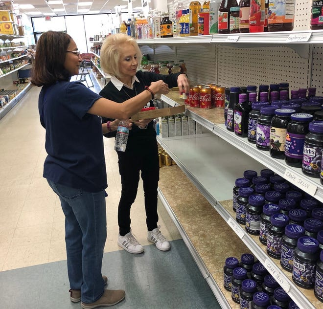 Janet Giordano (right), executive director of the Cherry Hill Food Pantry, stocks shelves with the help of volunteer Kalai Arulan. The pantry found a new home after learning it would have to leave its current space, but that deal has now fallen through.