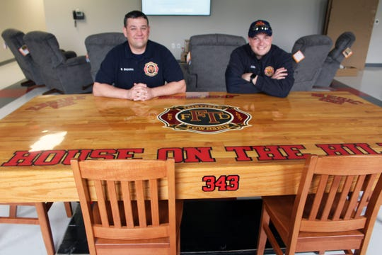 Fairfield Township firefighters Jacob Oakes, left, and Bryon Baumann sit at a table they built with Jason Agoston in 2011 that they brought over from the Tylersville Road station.