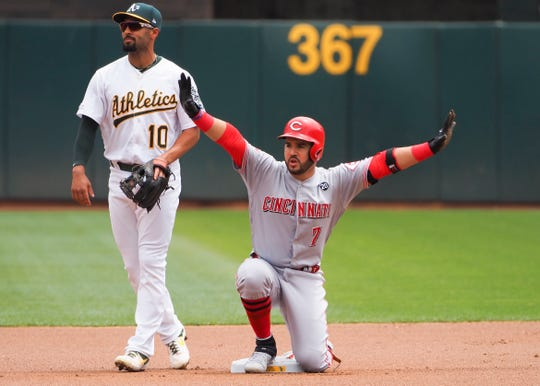 May 9, 2019; Oakland, CA, USA; Cincinnati Reds third baseman Eugenio Suarez (7) reacts at second base after hitting a double as Oakland Athletics shortstop Marcus Semien (10) looks on during the first inning at Oakland Coliseum. Mandatory Credit: Kelley L Cox-USA TODAY Sports