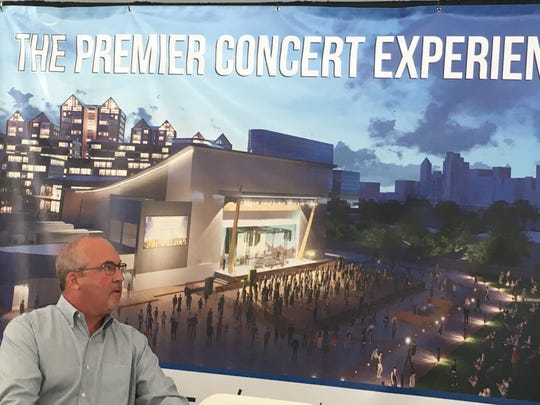 Scott Stienecker, founder and CEO of PromoWest Productions, in front of a rendering of a planned Newport, Ky., concert venue