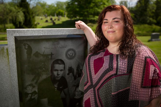 Lexie Back, 19, of Carlise, Ohio, poses at the gravesite of her brother Justin Back at Miami Cemetery in Waynesville, Ohio, on Wednesday, May 8, 2019. Justin Back was murdered in 2014, when he was 18 years old, by two men who had previously been childhood friends. Since her brother's death Lexie has entered the mortuary profession as she believes it's a way to help families say goodbye to their loved ones.