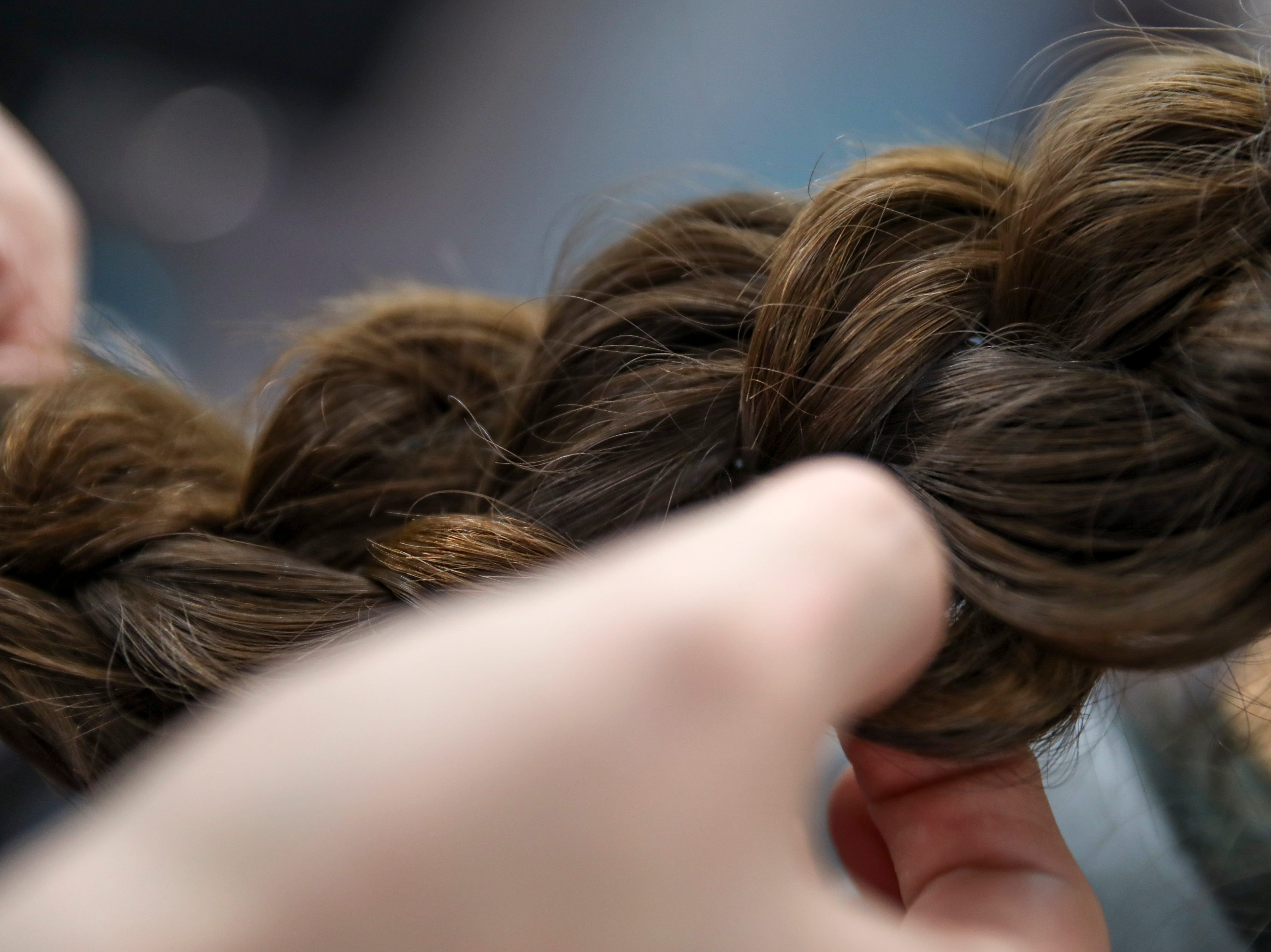 Christina West, a stylist at Tiffany's, braids the hair of Mia Lopez at Tiffany's Hair Spa in Clarksville, Tenn., on Saturday, May 4, 2019.