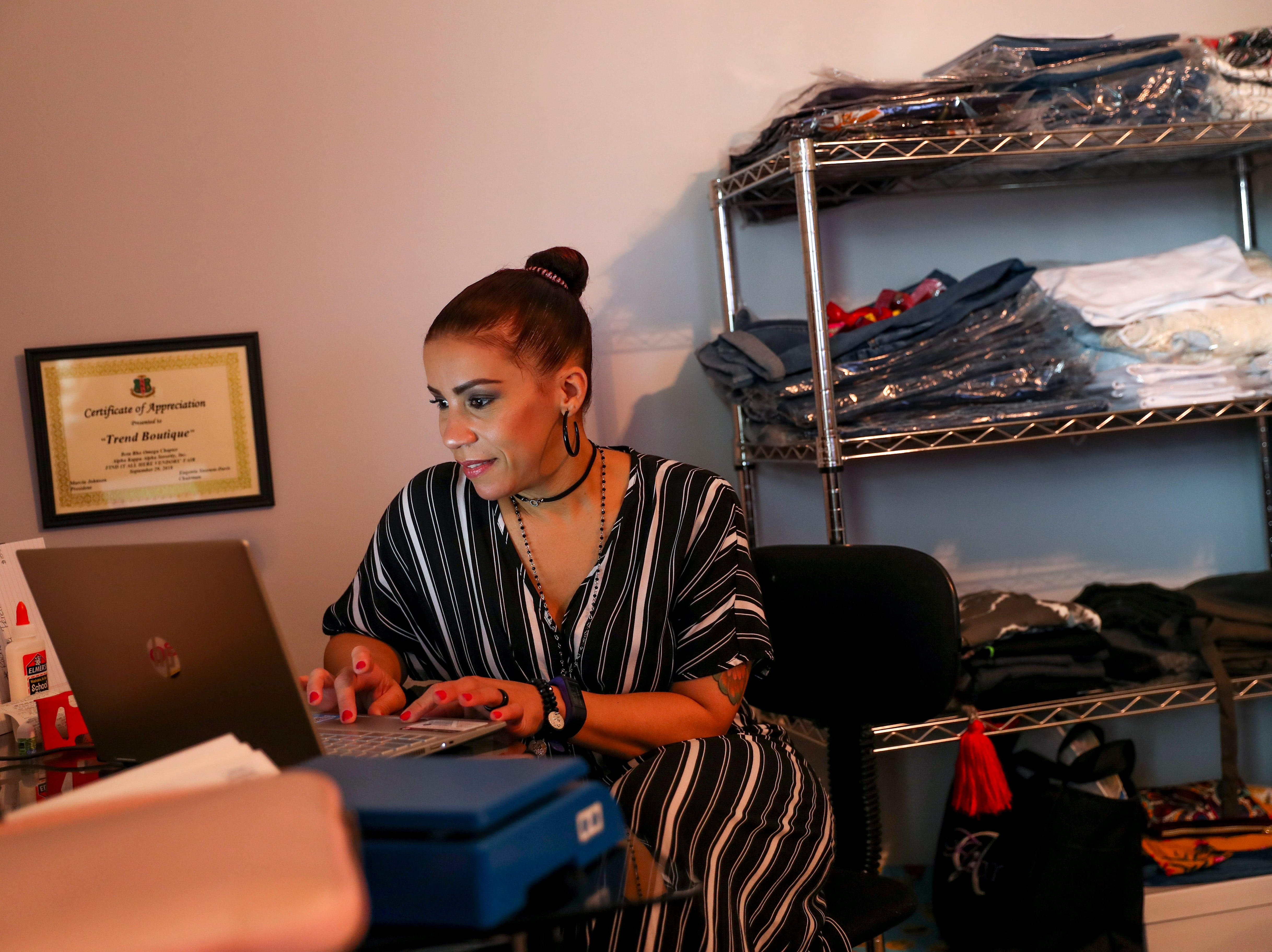 Ambar Tejada monitors her online business while two girls from Northeast High are prepared for prom at the Tejada household in Clarksville, Tenn., on Saturday, May 4, 2019.