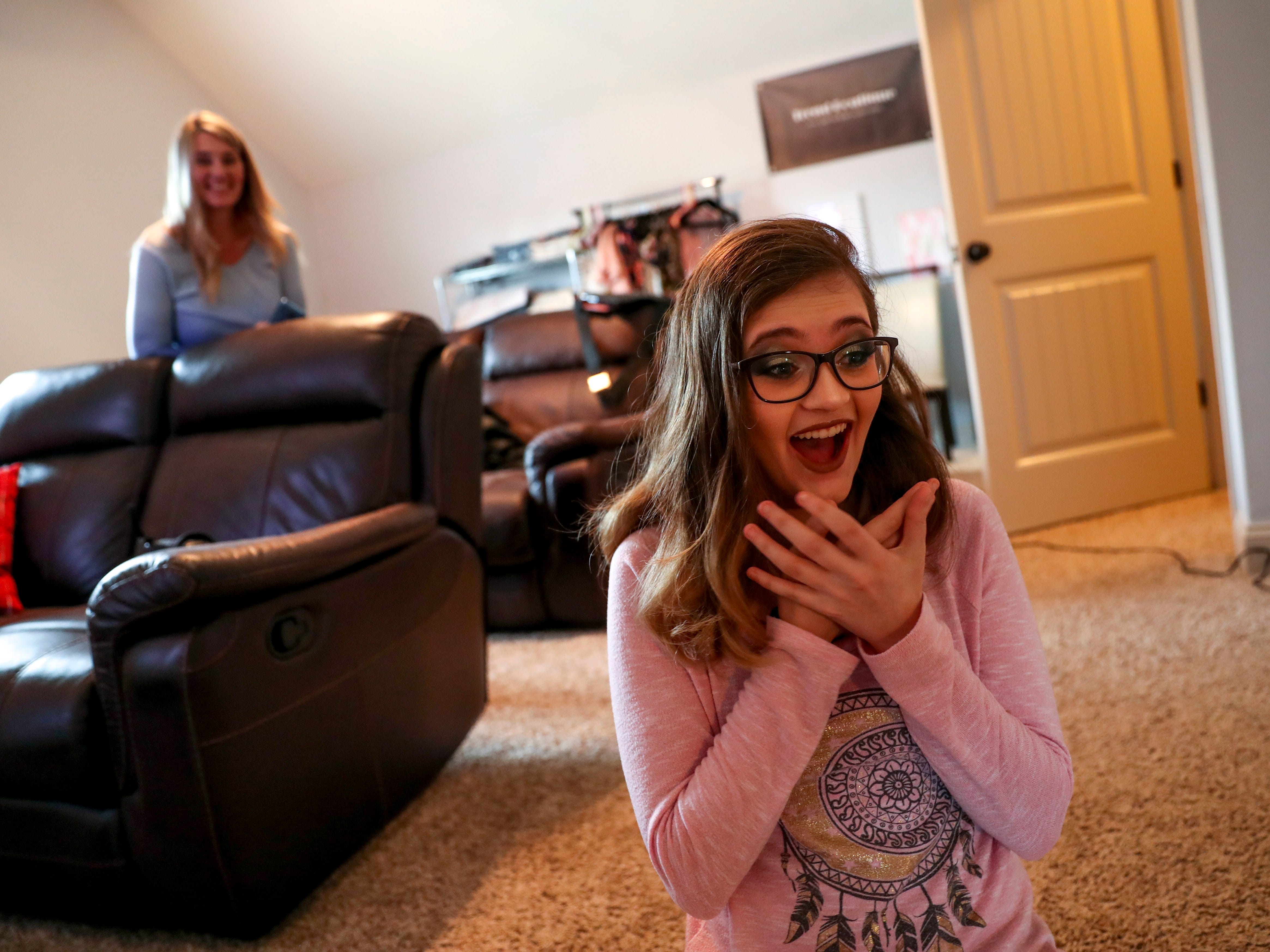 Madison Russell falls to her knees in excitement reacting to the makeup done for her prom at the Tejada household in Clarksville, Tenn., on Saturday, May 4, 2019.