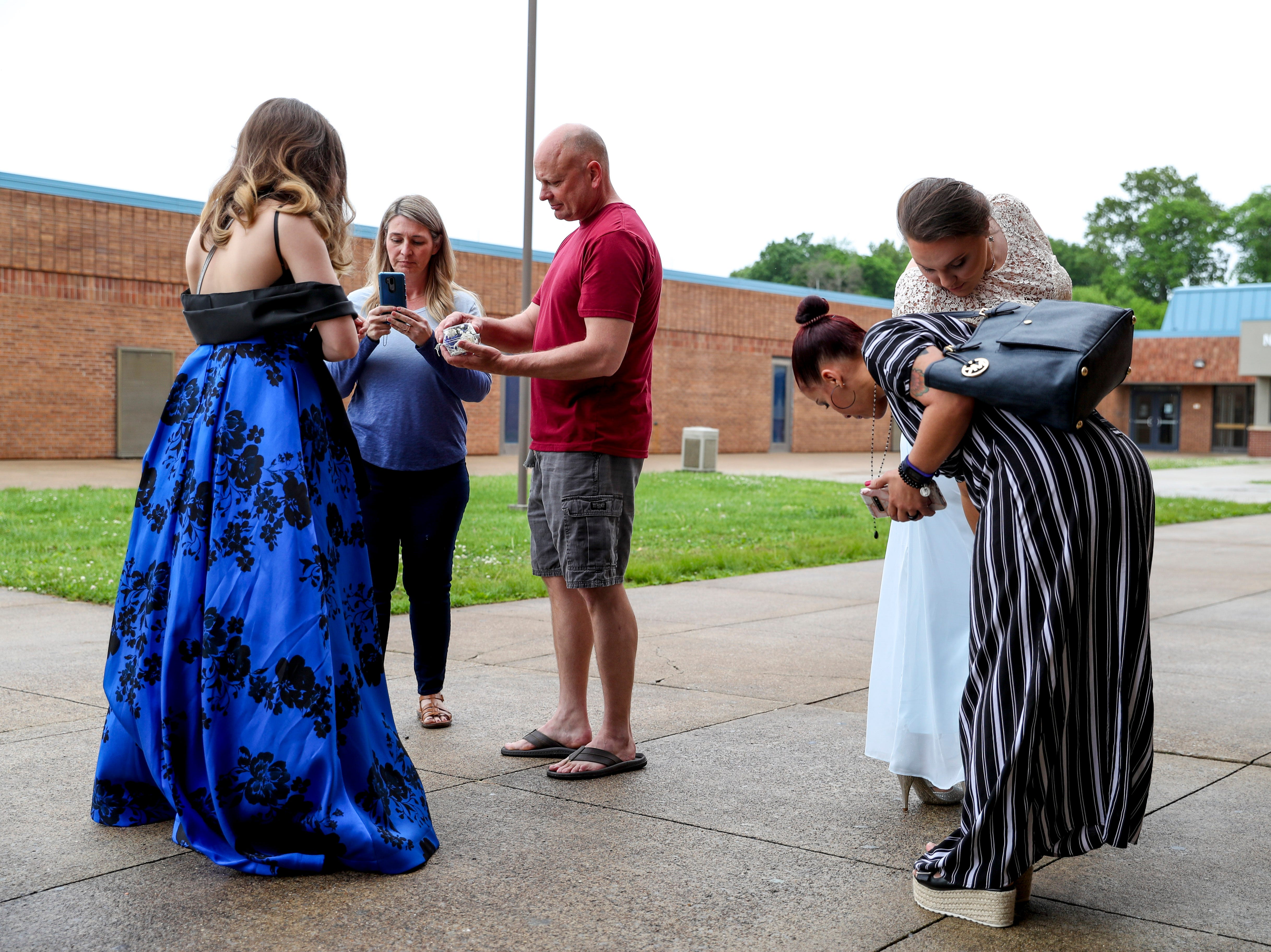 Ambar Tejada, right, adjusts Mia Lopez's dress while the Russell's take photos of their daughter at Northeast High School in Clarksville, Tenn., on Saturday, May 4, 2019.