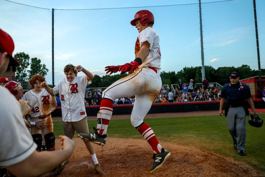 Rossview's Ty Garrett (31) leaps into a crowd of players welcoming him at home plate after a home run in a TSSAA baseball game between Rossview and Clarksville at Rossview High School in Clarksville, Tenn., on Wednesday, May 8, 2019.