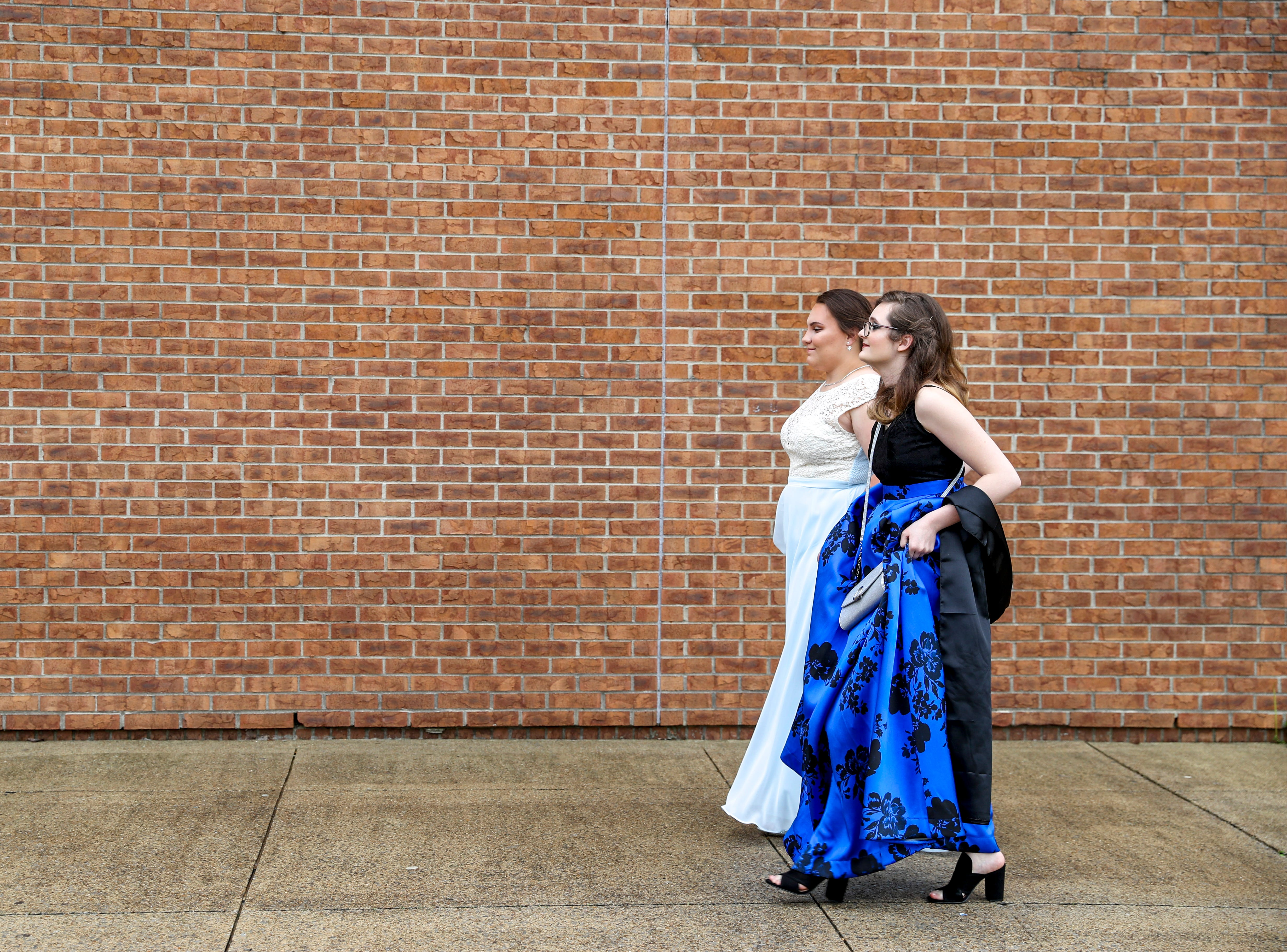 Madison Russell and Mia Lopez walk down the sidewalk heading to the red carpet at Northeast High School in Clarksville, Tenn., on Saturday, May 4, 2019.