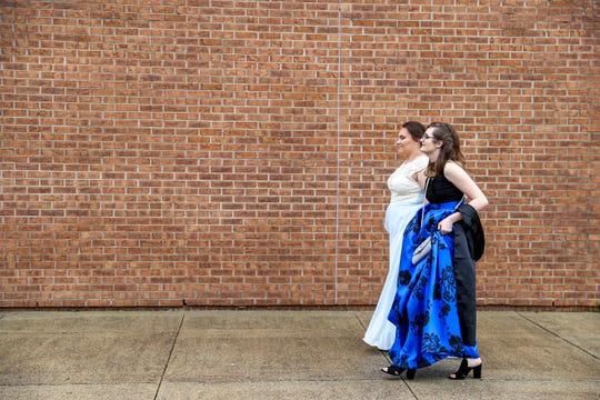 Madison Russell and Mia Lopez walk down the sidewalk heading to the red carpet at Northeast High School on Saturday.