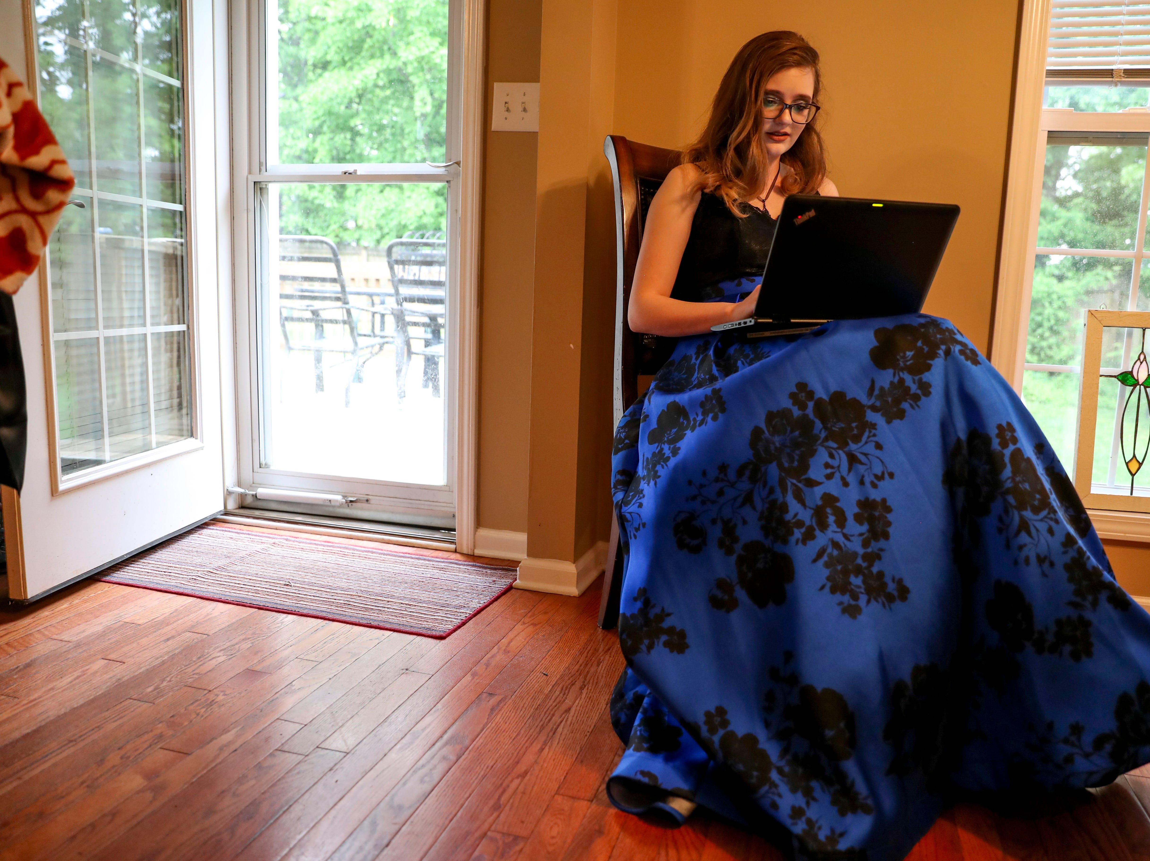 Madison Russell takes the time between makeup and putting on her dress and when she had to leave for prom to work on an essay for her AP Language class at the Russell household in Clarksville, Tenn., on Saturday, May 4, 2019.