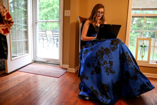 Madison Russell takes the time between makeup and putting on her dress and when she had to leave for prom to work on an essay for her AP Language class at the Russell household in Clarksville on Saturday.