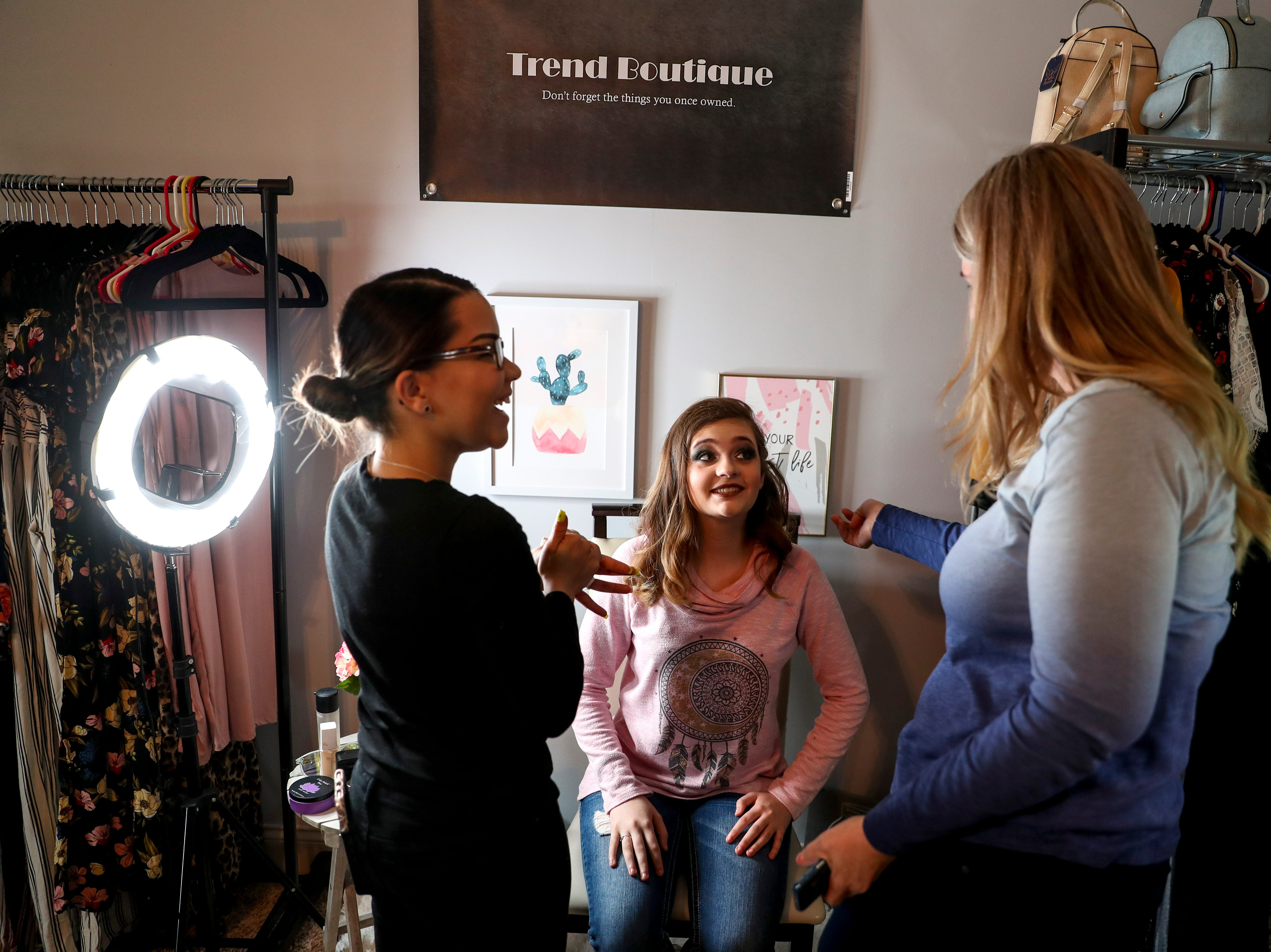 Madison Russell, center, looks up to her mom Dessarae Russell, right, after the finishing touches of makeup are put on by Miloshky Rodriguez, left, at the Tejada household in Clarksville, Tenn., on Saturday, May 4, 2019.