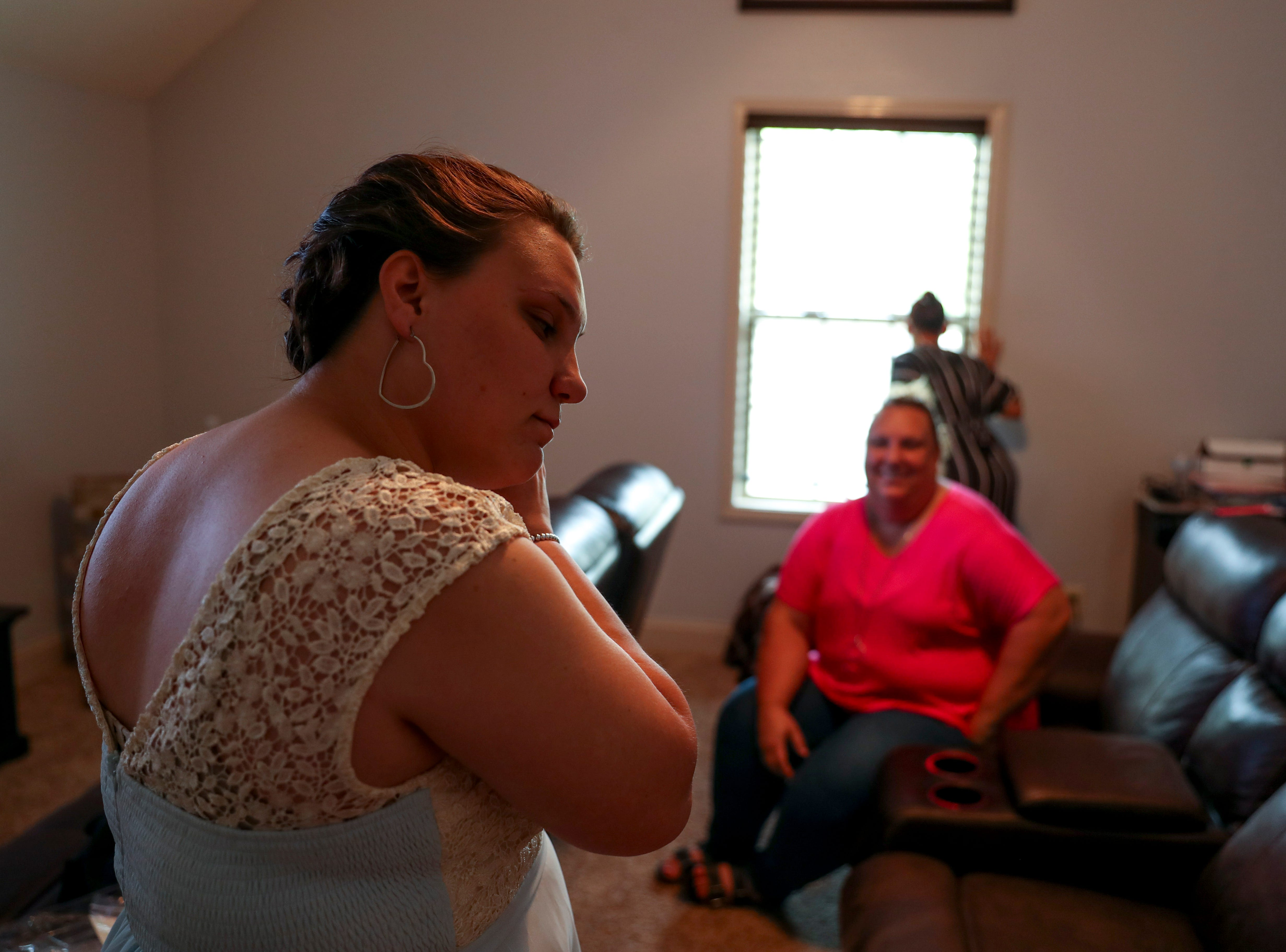 Mia Lopez tries to put on her earrings before sitting down for makeup at the Tejada household in Clarksville, Tenn., on Saturday, May 4, 2019.