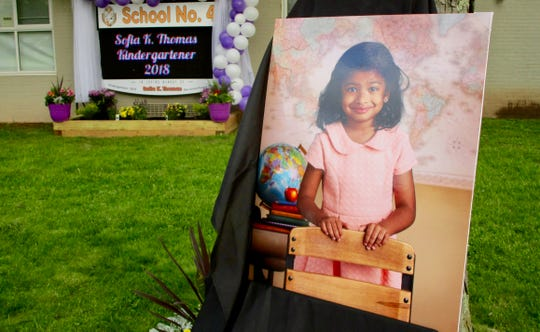 A photo of Sofia Thomas stood in front of an electronic display board during a ceremony dedicating the sign in her memory.