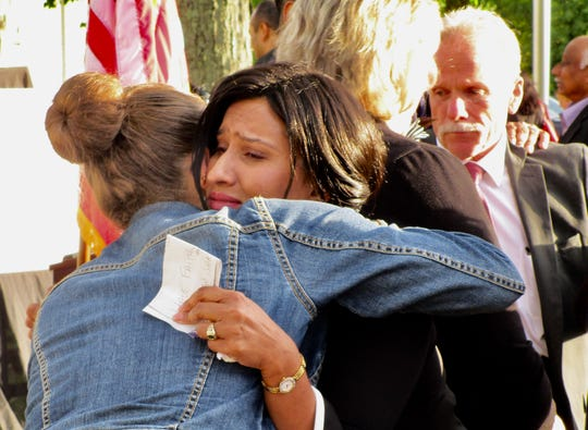 "Tini Thomas, mother of Sofia Thomas, being hugged by School No. 4 music teacher Katherine Thode after the ceremony. Tini Thomas is holding notes from her speech, which include the words, ""Have faith."""