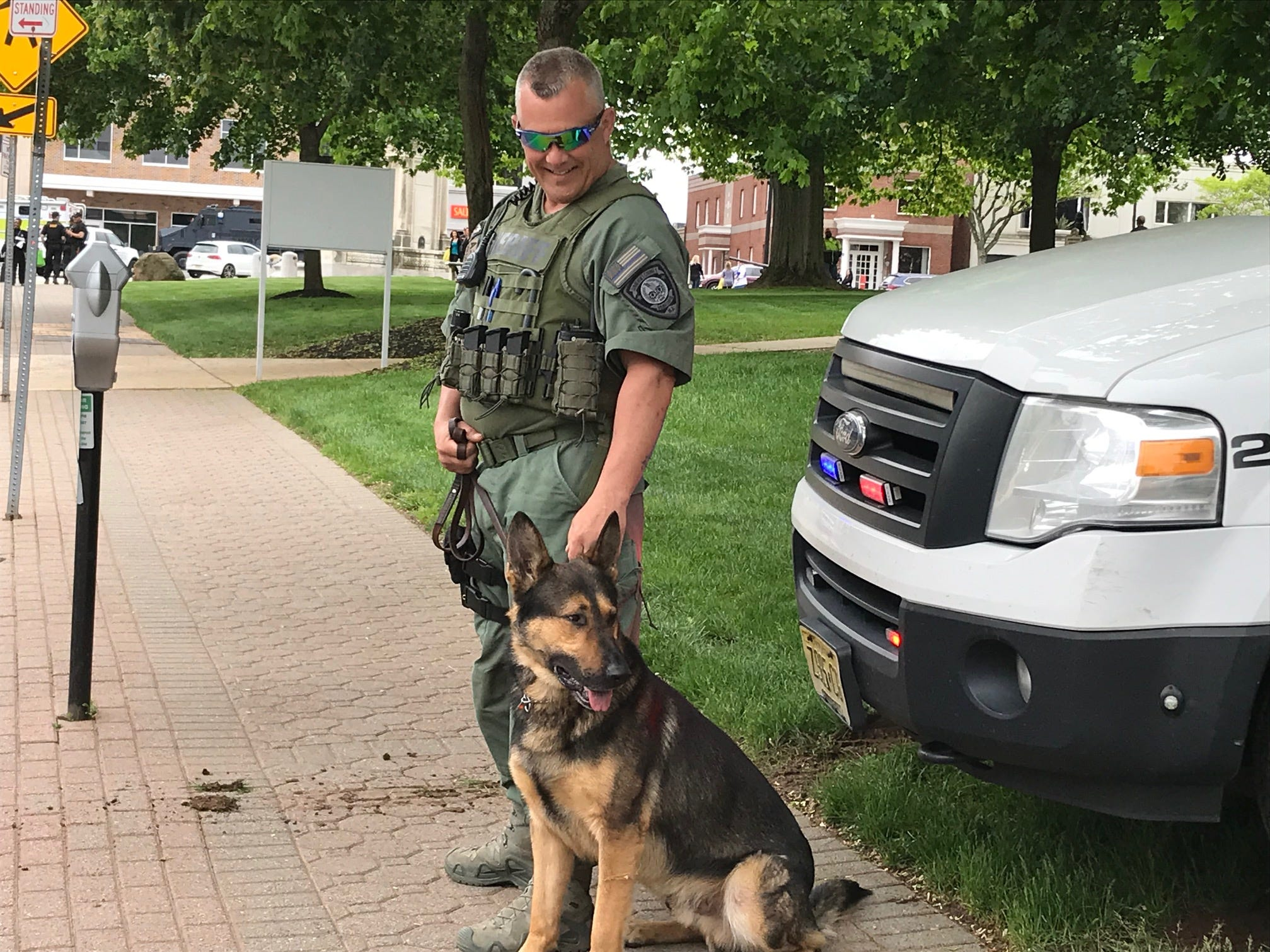 A police K-9 officer and his K-9 partner await the arrival of the Police Unity Tour in Somerville.