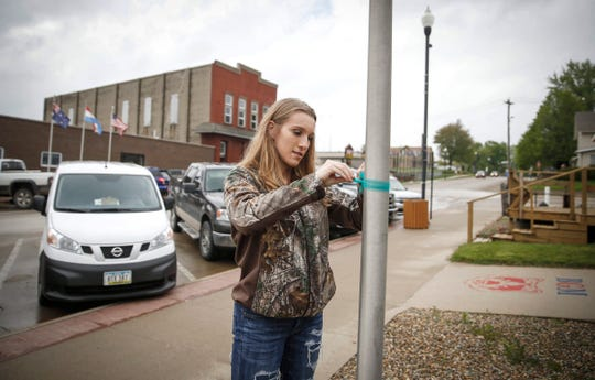 Hannah Vokoun, a senior at BGM High School, ties a ribbon onto a flagpole in recognition of what would have been the 21st birthday of Mollie Tibbitts on Wednesday, May 8, 2019, in Brooklyn. Members of the high school spent the afternoon going around the community performing random acts of kindness to pay tribute to the memory of Tibbetts, who was found stabbed to death last August.