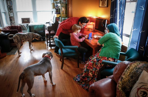 Erin and Kelly Meek play a game with their adopted son, Griffin, 6, as their dogs join in on Tuesday, May 7, 2019, at their home in Des Moines.