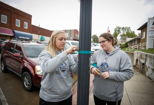 Rylie Gritsch, left, and Maycee Cline, both seniors at BGM High School, tie a ribbon onto a flagpole in recognition what would have been the 21st birthday of Mollie Tibbitts on Wednesday, May 8, 2019, in Brooklyn. Members of the high school spent the afternoon going around the community performing random acts of kindness to pay tribute to the memory of Tibbetts, who was found stabbed to death last August.