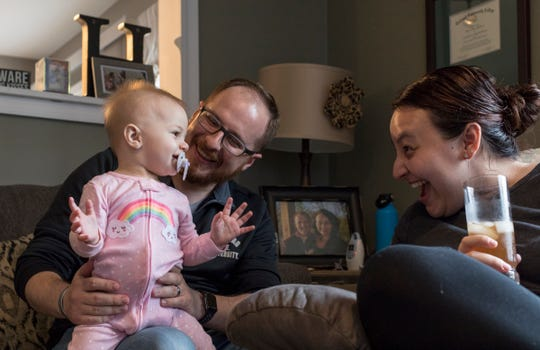 L to R:  Reagan Holman, 9-months, plays with her father Chris Holman, 31 and mother Becky Holman, 27 after her father returns from classes at Oakland University at their Waterford Mich.home, Wednesday, May 8, 2019.