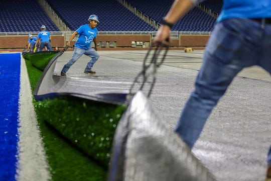 A FieldTurf crews pulls back the panel exposing the FieldTurf Classic HD system they are installing at Ford Field in Detroit, photographed on Thursday, May 9, 2019. The installation is expected to take four weeks and started on May 1st.