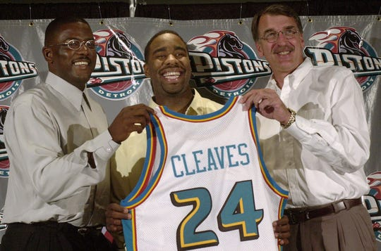 Mateen Cleaves, center, holds a Detroit Pistons jersey with his high school number with president of basketball operations Joe Dumars, left, and head coach George Irvine at the Palace in Auburn Hills, Mich., during a news conference.    DTP101