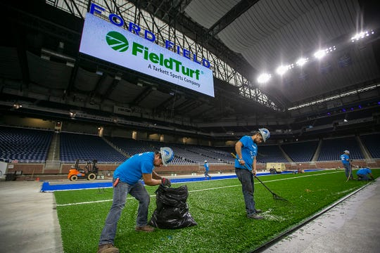A team rakes up and collects clippings of artificial turf that was sheared off during installation of FieldTurf Classic HD system at the Detroit Lions' Ford Field in Detroit on Thursday, May 9, 2019. The installation is expected to take four weeks and started on May 1st.